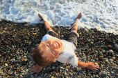 Sitting Teenager Boy Looking Upwards On Stone Seacoast, Wets Feet In Water, Sitting By Back