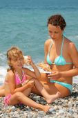 Beautiful Woman With Pretty Little Girl Has Leant Seashell Bowl To An Ear On Stone Seacoast