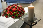 stock photo of grieving  - A coffin with a flower arrangement in a morgue and a burning candle in front - JPG