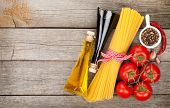 Pasta, tomatoes and spices on wooden table background with copy space