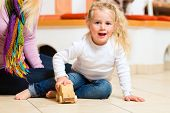 Girl sitting with mother on house floor playing with wooden toy car