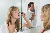 Close-up of a beautiful young woman applying mascara in the bathroom at home