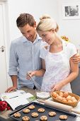 Young couple looking at cook book and preparing cookies in the kitchen at home