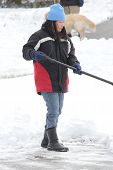 foto of snow shovel  - Lady shoveling the deep snow off her driveway after a snow storm - JPG