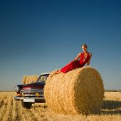 Girl Lying On Straw Bale With Retro Car Background