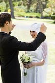 Young loving groom lifting veil of bride in park