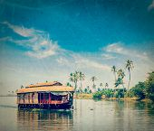 Vintage retro hipster style travel image of travel tourism Kerala background - houseboat on Kerala backwaters with grunge texture overlaid. Kerala, India