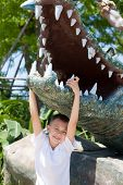 Boy hung on the jaw of a crocodile sculpture.