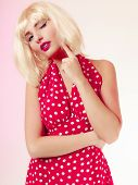 Thoughtful Girl In Blond Wig And Retro Red Dress Winking.