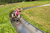 Excited young couples enjoying alpine coaster luge during summer