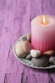 Composition with spa stones, candle  on color wooden table, on light background
