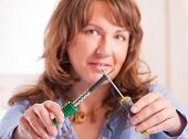 Woman holding soldering tool and screwdriver
