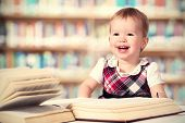 Happy Baby Girl Reading A Book In A Library