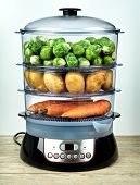 Healthy food in steamer, steam cooker with potatoes, carrots and brussels sprouts