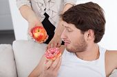Man Choosing Donut Instead Of Apple