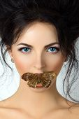 Beauty Portrait Of Young Woman With Mouth Covered With Butterfly