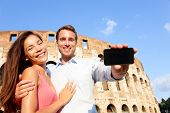 Couple showing smartphone in Rome by Colosseum in Italy. Happy lovers on honeymoon sightseeing Colis