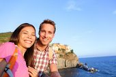 Selfie - couple in love in Cinque Terre, Italy. Romantic couple taking self portrait photo on holidays travel. Young man and woman backpackers on vacation in Manarola, Cinque Terre, Liguria, Italy