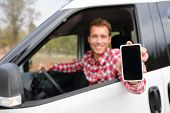 Smart phone man in car driving showing smartphone display smiling happy. Male driver using apps show