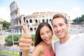Selfie - Romantic travel couple by Coliseum, Rome, Italy. Happy lovers on honeymoon sightseeing havi
