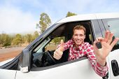 Car driver showing car keys and thumbs up happy. Young man holding car keys for new car. Rental cars or drivers licence concept with male driving in beautiful nature on road trip.