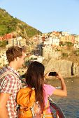 Couple taking photo on smartphone in Cinque Terre. Romantic couple taking photo using smart phone on