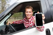 Smartphone man in car driving showing smart phone display smiling happy. Male driver using app showi