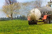 a tractor with manure fertilizes a field in autumn
