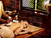 foto of ayurveda  - Woman having Ayurveda massage with pouch of rice - JPG