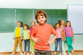 Boy stands in front of kids near blackboard