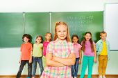 Girl stands with arms crossed near blackboard