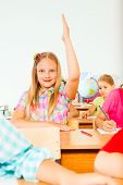 Blond girl holds hand up in class and smiles