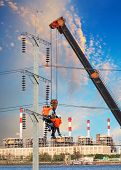 Electrician Worker Working On High Voltage Electric Pole With Crane Against Factory Building Backgro