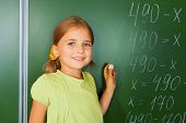 Cute girl with chalk in hand near blackboard