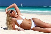 stock photo of swimsuit model  - Young female enjoying sunny day on tropical beach - JPG