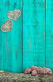 Wooden hearts hanging on antique teal blue fence with log and flowers border