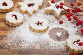 pic of linzer  - Christmas Linzer Cookies being decorated with powdered sugar on a wooden background.