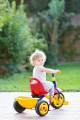 Cute Happy Smiling Baby Girl Riding Her First Bicycle In The Back Yard Of The House On A Sunny Day