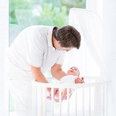 Young Father Putting His Newborn Baby In White Round Crib Standing At A Big Window