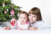 Happy Brother And Baby Sister Playing Together Under A Christmas Tree