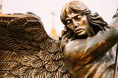 Statue Of Archangel Michael With Outstretched Wings Before Red Catholic Church
