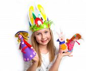 Little girl demonstrating her cruft work Easter bonnet, paper dolls and reindeer