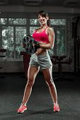 Fitness Woman Swinging Kettle Bell At Gym