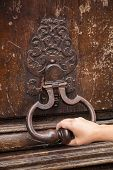 Hand And Old Rusted Knocker On Brown Wooden Door In Paris, France