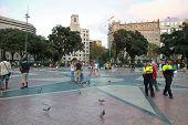 Ordinary People And Policemen Walking On The Placa De Catalunya In Barcelona