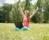 Happy internet shopping woman online with laptop and credit card sitting outdoor on green grass. Int