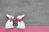 Easter rabbits decoration in interior on a wooden background in red and white checkered.