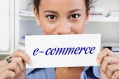 Hands of woman holding sign: E-commerce
