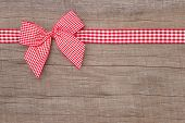 Top view of checked ribbon decoration on wooden background for christmas.
