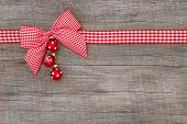 Top view of checked ribbon decoration with balls on wooden background for a christmas card, christmas voucher or coupon